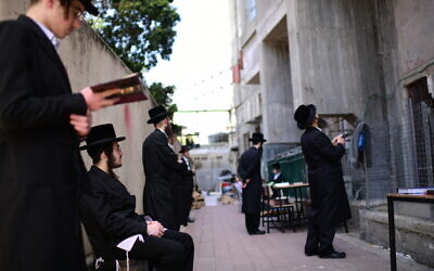 Ultra-Orthodox Jewish men pray outside a closed yeshiva, in the town of Bnei Brak, on March 26, 2020. (Tomer Neuberg/Flash90)