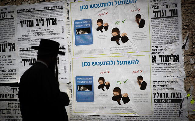 "Ultra-Orthodox Jewish men looks at ""Pashkvil""- information poster about the Coronavirus (COVID-19) in the neighborhood of Meah Shearim, Jerusalem, on March 27, 2020. (Yonatan Sindel/Flash90)"
