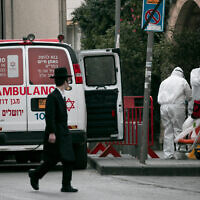 Magen David Adom paramedics in protective clothing are seen in Jerusalem on March 28, 2020. (Olivier Fitoussi/Flash90)