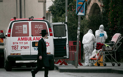 Magen David Adom paramedics, wearing protective clothing as a preventive measure against the coronavirus leave the scene of an emergency call in Jerusalem on March 28, 2020 (Olivier Fitoussi/Flash90)