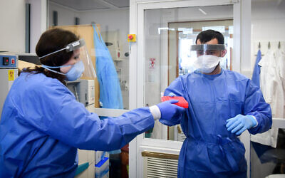 Medical team members at the Barzilay hospital, in the southern Israeli city of Ashkelon, wear protective gear as they handle a coronavirus test sample on March 29, 2020. (Flash90)