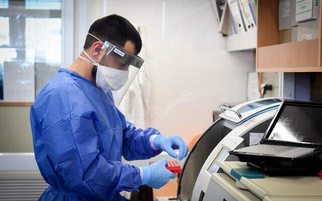Os membros da equipe médica do hospital Barzilay, na cidade de Ashkelon, no sul de Israel, usam equipamentos de proteção ao lidar com uma amostra de teste de coronavírus em 29 de março de 2020. (Flash90)