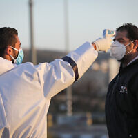 Palestinian medical employees disinfect Palestinian workers who came back from working in Israel at the entrance to the West Bank village of Hussan, on March 29, 2020, in order to stop the spread of the coronavirus.  (Nati Shohat/Flash90)