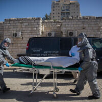 Illustrative: Funeral workers wearing protective clothes carry the body of a patient who died from the coronavirus (COVID-19), at the Shamgar Funeral Home in Jerusalem on March 29, 2020. (Yonatan Sindel/Flash90)