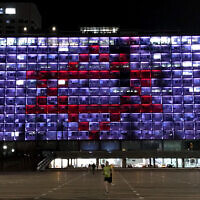 Tel Aviv city hall is lit up with the Magen David Adom logo to show support to medical workers battling the coronavirus, March 30, 2020. (Avshalom Sassoni/Flash90)