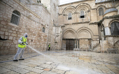 Jerusalem Municipality employees disinfect the forecourt outside the closed gate of Church of the Holy Sepulchre  as a measure against the spread of coronavirus on March 30 2020. (Olivier Fitoussi/Flash90)