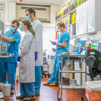 Technicians carry out a diagnostic test for coronavirus in a lab at Rambam Hospital in Haifa, on March 30, 2020. (Yossi Aloni/ Flash90)