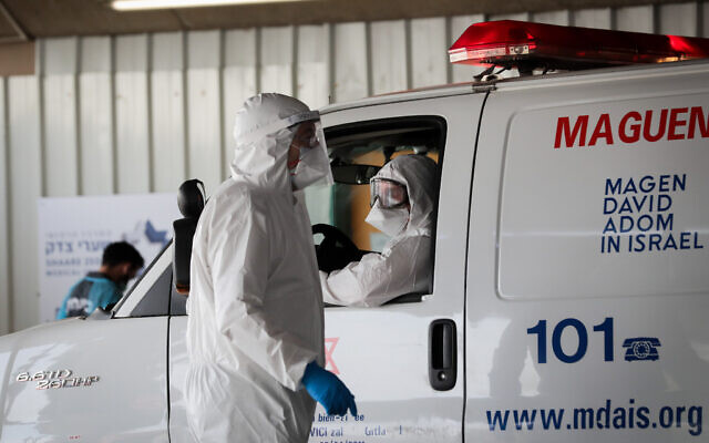Magen David Adom workers wearing protective clothing as a preventive measure against the coronavirus, seen as they evacuating a man with suspicion for coronavirus at Shaare Zedek hospital in Jerusalem on March 30, 2020 (Yossi Zamir/Flash90)