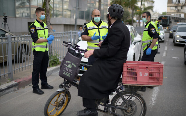 Police officers man a checkpoint at an entrance to the predominantly ultra-Orthodox city of Bnei Brak, which has seen a large number of coronavirus cases, on March 31, 2020. (Gili Yaari/Flash90)