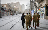 A police officer walks with soldiers as they patrol Jerusalem city center to enforce a partial lockdown against the spread of the coronavirus on March 31, 2020. (Olivier Fitoussi/Flash90)