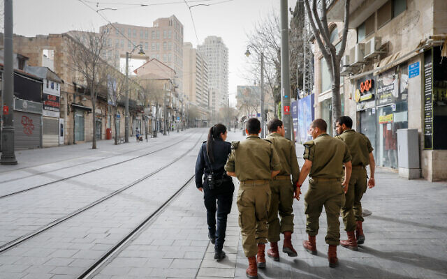 A Police officer walks with soldiers as they patrol Jerusalem city center to enforce a partial lockdown in order to prevent the spread of the coronavirus on March 31, 2020. (Olivier Fitoussi/Flash90)