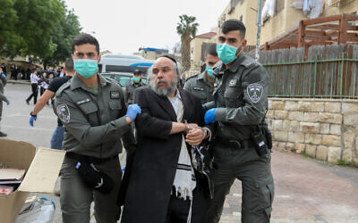 Police officers detain a man in Beit Shemesh while enforcing social distancing rules on March 31, 2020.  (Yaakov Lederman/Flash90)