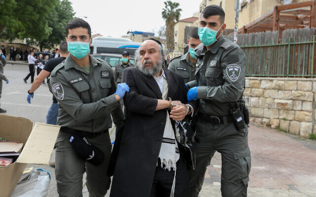 ILLUSTRATIVE: Police officers detain a man in Beit Shemesh while enforcing social distancing rules on March 31, 2020. (Yaakov Lederman/Flash90)