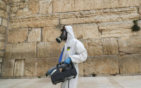 Cleaning workers disinfect the Western wall due to the COVID-19 virus in the Old City of Jerusalem as a measure against the spread of coronavirus on March 31 2020. (Yonatan Sindel/Flash90)