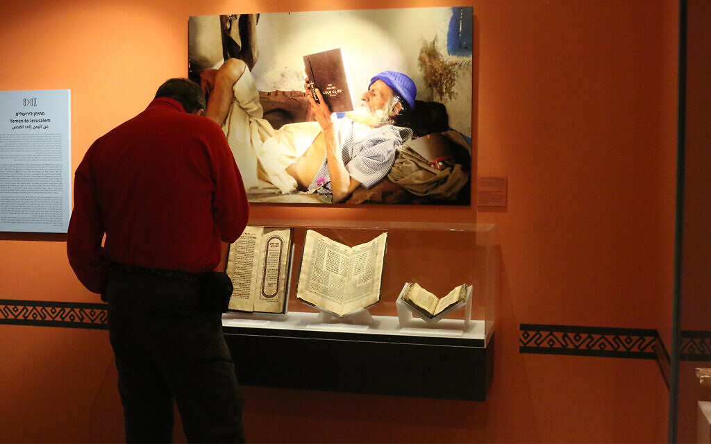 A visitor at the Bible Lands Museum in front of a photo by Naftali Hilger depicting a Yemenite elder reading a book upside down. (Shmuel Bar-Am)