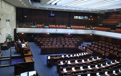 A nearly empty plenum, due to restrictions against the coronavirus, is seen at the swearing-in of the 23rd Knesset, March 16, 2020. (Gideon Sharon/Knesset Spokesperson)