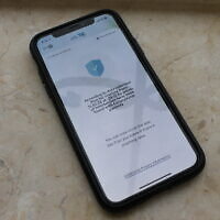 An iPhone running the Health Ministry's Hamagen app, which aims to track the spread of the novel coronavirus and warn users if they've interacted with someone infected. (Sam Sokol)