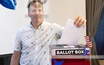 The first voter Gary Gray from New York casts his ballot on the Super Tuesday, for U.S. Democrats Abroad multi-location global primary at Foreign Correspondents' Club of Thailand, March 3, 2020. (AP Photo/Sakchai Lalit)