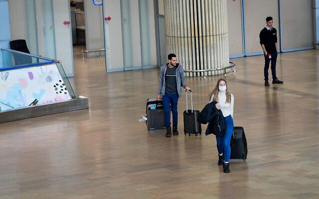 People wearing face masks for fear of the coronavirus arrive at Ben Gurion International Airport near Tel Aviv, March 10, 2020. (Avshalom Sassoni/Flash90)
