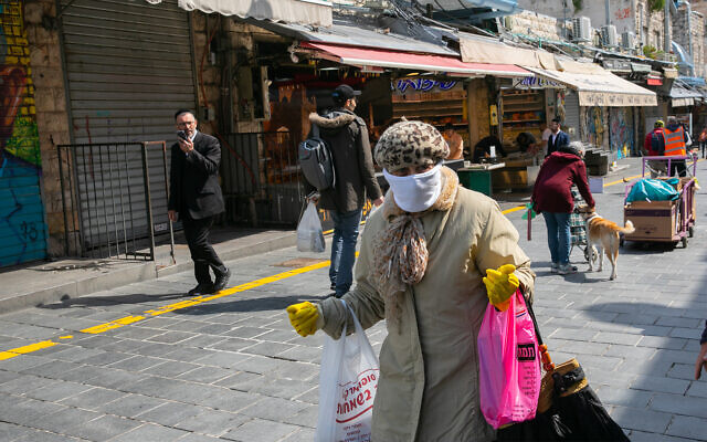 An Israeli woman wearing a face mask for fear of the coronavirus at the Mahane Yehuda Market in Jerusalem, March 22, 2020. (Olivier Fitoussi/Flash90)