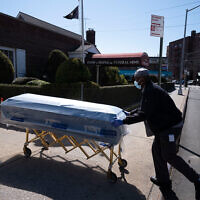 A worker delivers caskets to the Gerard Neufeld Funeral Home in the Queens borough of New York City, March 27, 2020. (AP/Mark Lennihan)