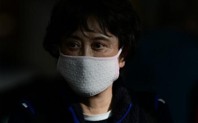 A woman wears a protective face mask amid coronavirus fears at the arrival hall of Ben Gurion Airport, near Tel Aviv, January 30, 2020. (Tomer Neuberg/Flash90)