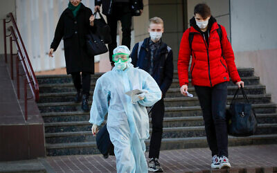 A medical worker wearing a protective suit assists students to an ambulance in Minsk, Belarus, March 13, 2020. (AP Photo/Sergei Grits)