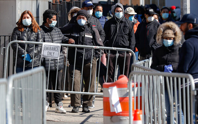 Patients wearing face masks and personal protective equipment wait on line for COVID-19 testing outside Elmhurst Hospital Center in New York, March 27, 2020. (AP/John Minchillo)
