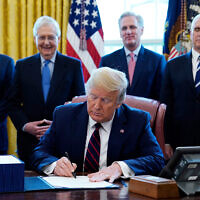US President Donald Trump signs the coronavirus stimulus relief package at the White House in Washington, DC, March 27, 2020. From left: Treasury Secretary Steven Mnuchin, Senate Majority Leader Mitch McConnell of Ky., House Minority Kevin McCarthy of Calif., and Vice President Mike Pence. (AP/Evan Vucci)