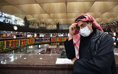 A Kuwaiti trader wearing a protective mask follows the market at the Boursa Kuwait stock exchange in Kuwait City, March 1, 2020. (Yasser al-Zayyat/AFP)