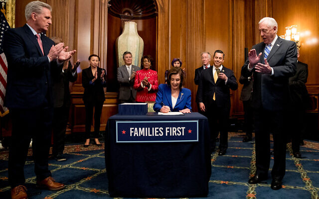House Speaker Nancy Pelosi of California, accompanied by House Minority Leader Kevin McCarthy of Calif., left, House Majority Leader Steny Hoyer of Maryland right, and other bipartisan legislators, signs the Coronavirus Aid, Relief, and Economic Security (CARES) Act after it passed in the House on Capitol Hill in Washington, DC, March 27, 2020. (AP/Andrew Harnik)