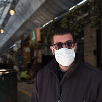 A guard at the shuttered Mahane Yehuda market in Jerusalem, March 29, 2020. (Nati Shohat/Flash90)