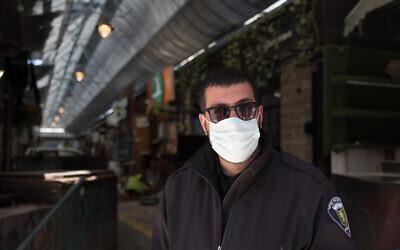 A guard at the shuttered Mahane Yehuda market in Jerusalem, March 29, 2020. (Nati Shohat/Flash90)