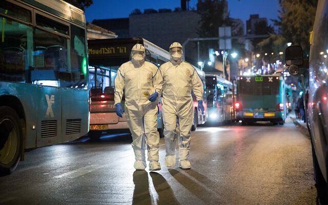 Medical workers wear protective suits as a preventive measure against the coronavirus, as they arrive to test a patient with symptoms, Jerusalem, March 16, 2020. (Yonatan Sindel/ Flash90)
