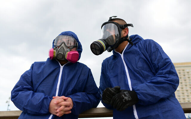 Workers wearing protective clothes disinfect a public playground in Bat Yam as part of measures to prevent the spread of the coronavirus, March 18, 2020. (Tomer Neuberg/Flash90)