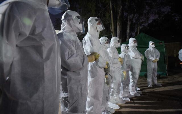 Workers at Sheba-Tel Hashomer Hospital wait for Israelis who were under coronavirus quarantine on the cruise ship Diamond Princess, in Japan, February 20, 2020. (Avshalom Sassoni/Flash90)