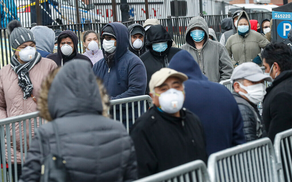 Patients wear personal protective equipment while maintaining social distancing as they wait in line for a COVID-19 test at Elmhurst Hospital Center in New York, March 25, 2020. (AP/John Minchillo)