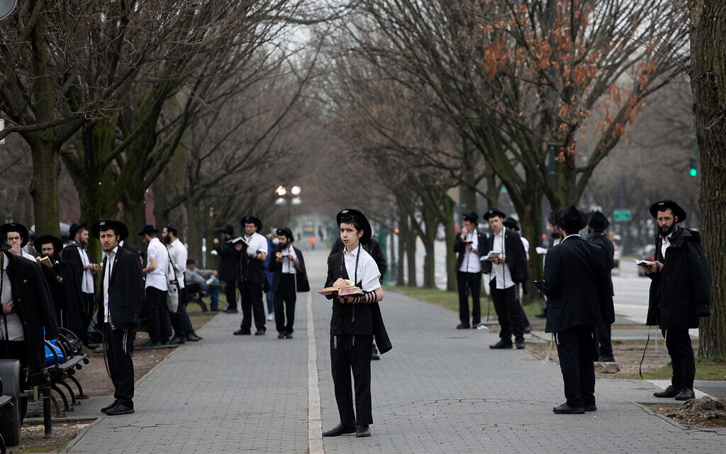 """Jewish men use """"social distancing"""" as they pray outside the Chabad Lubavitch World Headquarters in Brooklyn, New York, March 20, 2020. (AP/Mark Lennihan)"""