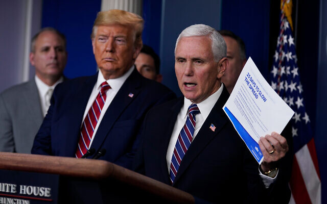 US President Donald Trump listens as Vice President Mike Pence speaks during a coronavirus task force briefing at the White House, March 20, 2020, in Washington. (AP/Evan Vucci)