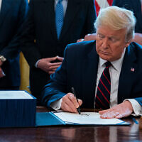 US President Donald Trump signs the coronavirus stimulus relief package in the Oval Office at the White House in Washington, DC, March 27, 2020. (AP/Evan Vucci)