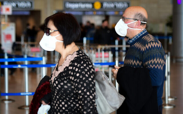 People wearing face masks for fear of the coronavirus at Ben Gurion International airport, February 27, 2020. (Avshalom Shoshani/Flash90)