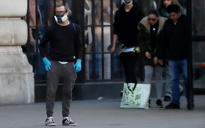 A man wearing a mask waits with other people at a bus stop in London, March 24, 2020. (AP Photo/Frank Augstein)
