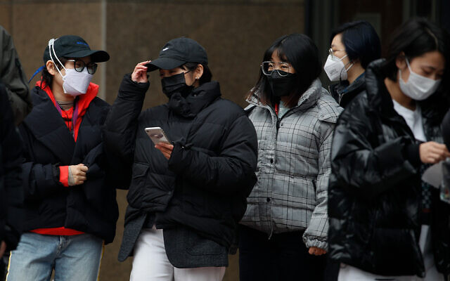Office workers wearing protective face masks during a lunch break in Beijing, China, February 24, 2020. (AP/Andy Wong)