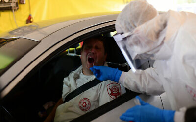 Magen David Adom personnel at a drive-through site to collect samples for coronavirus testing, Tel Aviv, March 20, 2020. (Tomer Neuberg/Flash90)