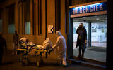 An elderly COVID-19 patient is transferred to an ambulance from a Hospital in Barcelona, Spain, March 27, 2020. (AP/Felipe Dana)