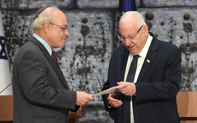 Central Elections Committee chairman Supreme Court Justice Neal Hendel, left, hands the official results of the elections to the 23rd Knesset to President Reuven Rivlin, at the President's House, March 11, 2020. (Mark Neyman/GPO)