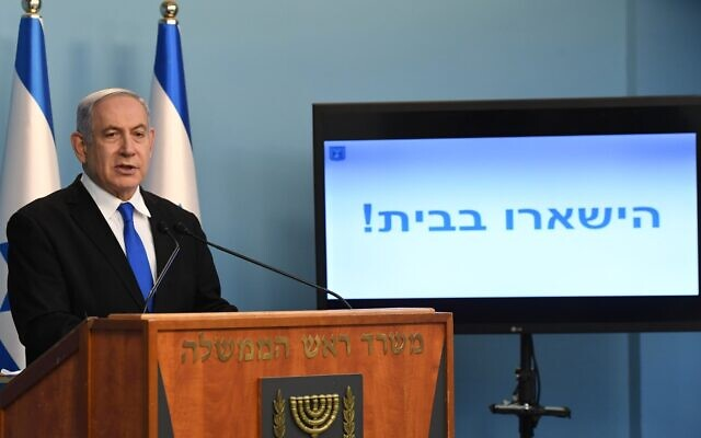 "Prime Minister Benjamin Netanyahu at a press conference on the coronavirus, March 17, 2020. The text on the screen reads: ""Stay home!""(Kobi Gideon/GPO)"