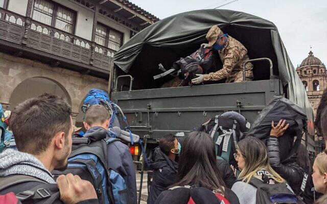 A Peruvian soldier unloads the bags of Israeli travelers at the airport in Peru's southeastern city of Cusco, March, 19, 2020. (Amsalem Tours)