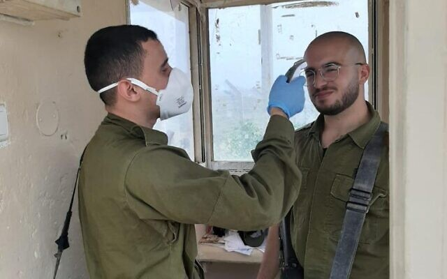 A soldier checks the temperature of a comrade as he enters a military base during the coronavirus pandemic in March 2020. (Israel Defense Forces)