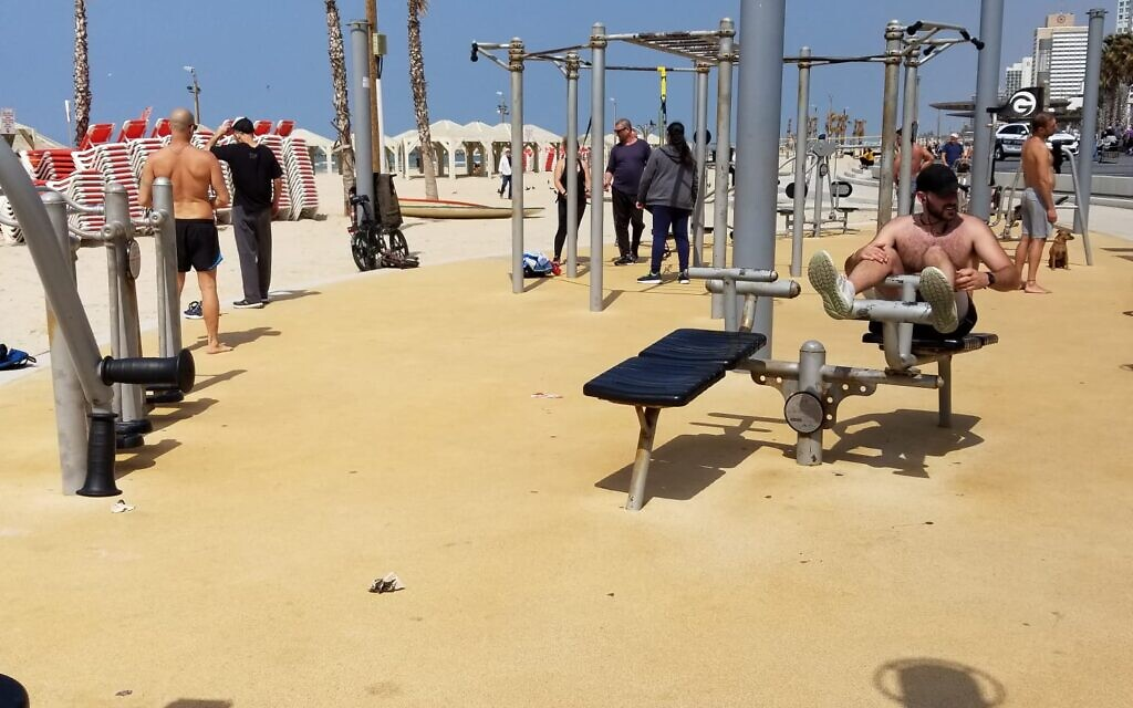 Persons working out at an outdoor gym in Tel Aviv on March 15, 2020. (Adam Rasgon/Times of Israel)